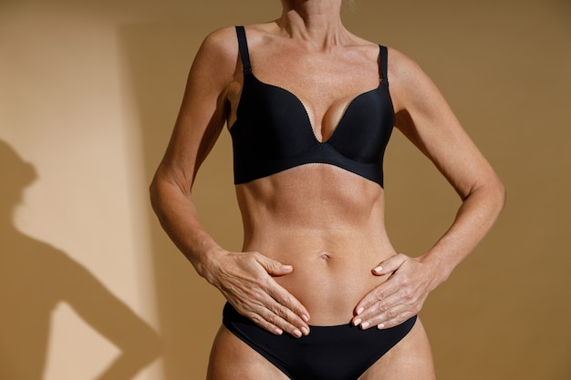 Cropped shot of perfect fit body of mature woman in black underwear holding hands on her stomach