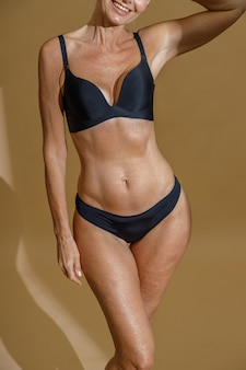 Cropped shot of perfect fit body of mature woman posing half naked in black underwear standing in