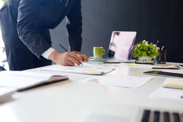 사업가 사무실에서 컴퓨터와 종이에 금융 작업의 총된 사진.