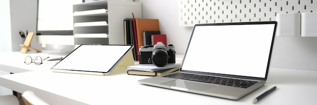 Cropped shot of photographer office desk with blank screen digital devices, office supplies and camera
