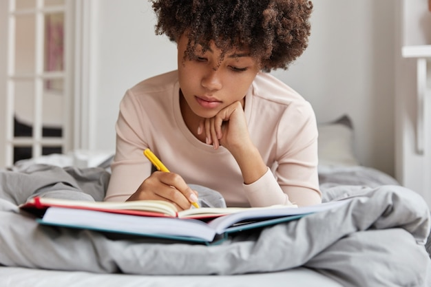 Ritagliata colpo di donna dalla pelle scura dall'aspetto piacevole scrive note nel taccuino dal libro, ha concentrato lo sguardo verso il basso, si trova sul letto comodo