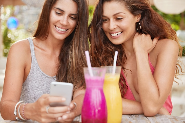 Cropped shot of pleased attractive women have fun together, look with intriguing expression at smart phone