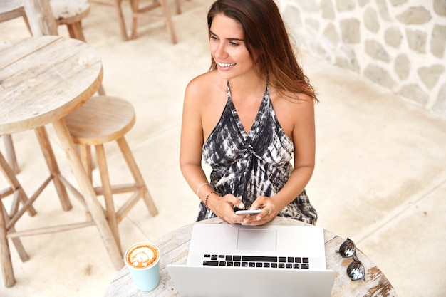 Cropped shot of pleased beautiful female model dressed in fashionable clothing, holds modern smart phone, sits in front of opened laptop, looks joyfully aside. people, rest and lifestyle concept