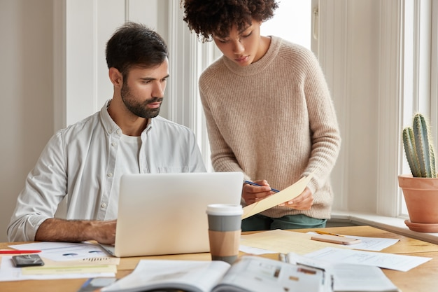 Cropped shot of pretty black woman dictates information to her assistant, work as team at cozy room