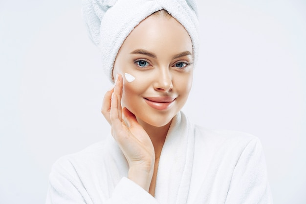 Cropped shot of pretty young woman applies cream for rejuvenation, healthy soft skin, uses cosmetic product, demonstrates nice effect of body lotion, wears comfortable soft white bath robe, towel