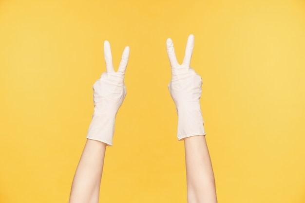 Cropped shot of raised hands in white rubber gloves forming peace gesture with four fingers, posing over orange background. hands gestures and signs concept