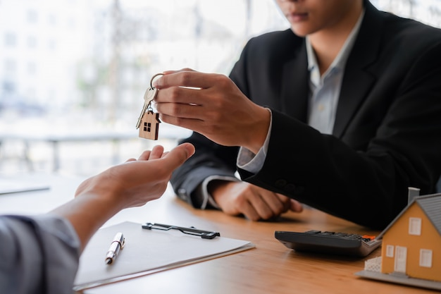 Cropped shot of real estate agent or banker giving a key to his customer.