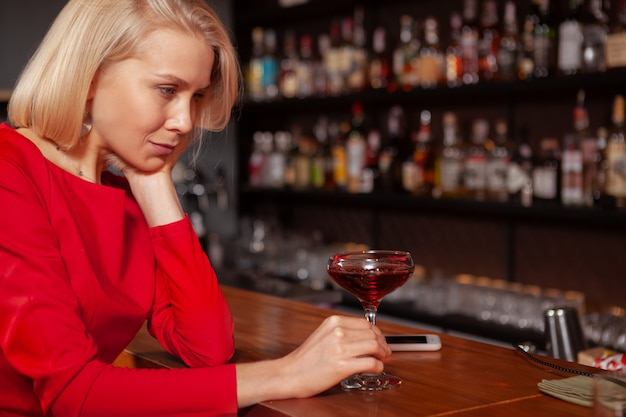 Cropped shot of a sad woman drinking at the bar. depressed woman having a cocktail alone at the restaurant