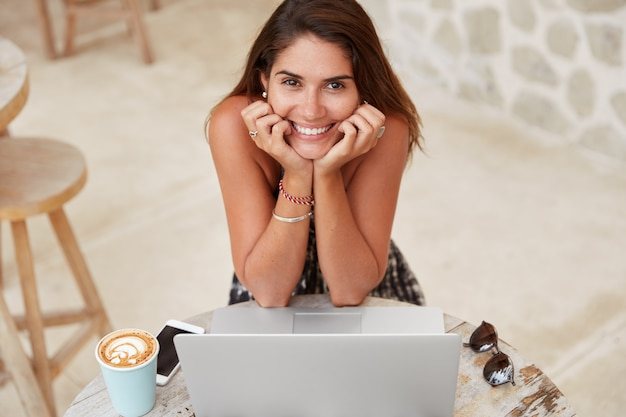 Cropped shot of satisfied young woman with pleased expression works on laptop computer in coffee shop, drinks aromatic cappuccino