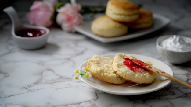 Cropped shot of scones with strawberry jam, clotted cream and copy space