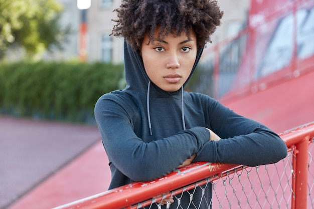 Cropped shot of serious dark skinned woman hipster has curly hair, dressed in sweatshirt with hoodie