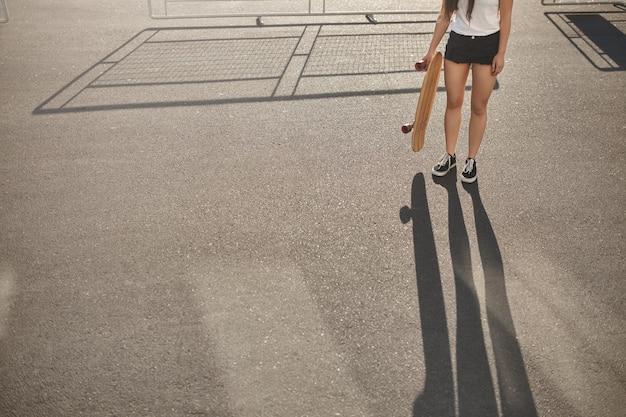 Обрезанный снимок фигуристка в шортах, кроссовках, практикующих скейтбординг