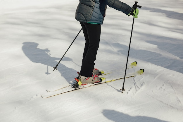 Cropped shot of a skier wearing skis standing on the snowy mountains