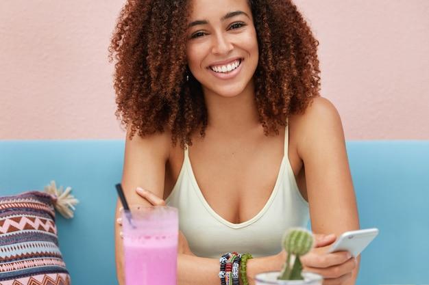 Ritagliata colpo di donna afroamericana dalla pelle scura sorridente felice tiene smart phone, naviga nei social network online