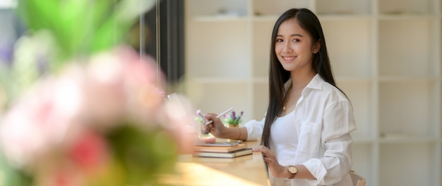 Cropped shot of smiling female university student sitting at wooden counter bar