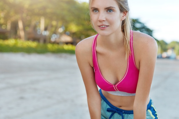 Cropped shot of sporty young woman in pink top and shorts, catches breath after long running, goes in for sport at sandy beach, has thoughtful expression. people and health motivation concept