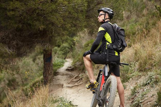 Ritagliata immagine di un elegante motociclista professionista in abbigliamento sportivo, casco e occhiali che riposa in mezzo al bosco con bicicletta elettrica nera motorizzata, ammirando la bellissima natura selvaggia che lo circonda
