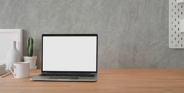 Cropped shot of stylish workplace with open blank screen laptop computer and office supplies on wooden table and loft grey wall