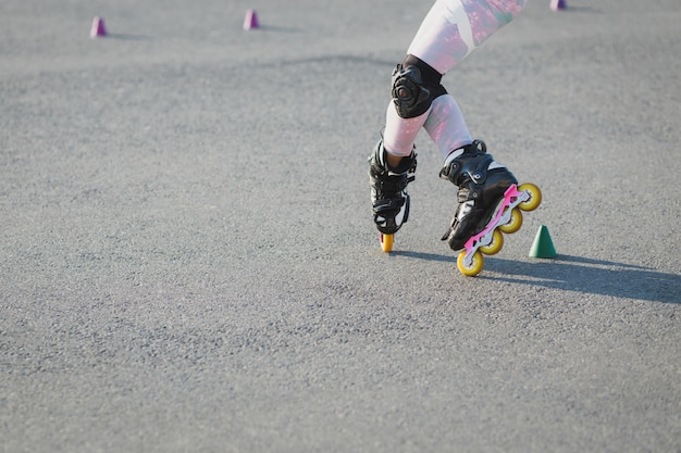 Cropped shot of teenager rollerblades on asphalt, has trial, wears rollerblade and protection on knees