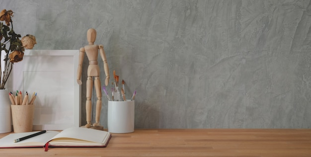 Cropped shot of trendy workplace with office supplies on wooden table and grey wall