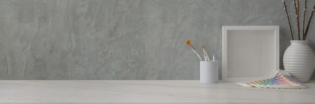 Cropped shot of trendy workspace with designer supplies and decorations on marble desk