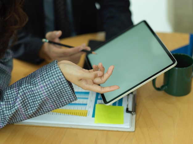 Cropped shot of two businessperson discussing on their work with digital tablet and paperwork in meeting room