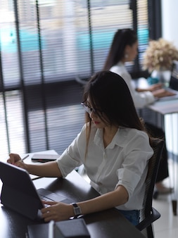 Cropped shot of two female office workers working with office supplies in office room