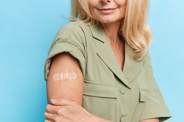 Cropped shot of unrecognizable blonde woman gets shot vaccination wears adhesive bandage on shoulder poses against blue wall