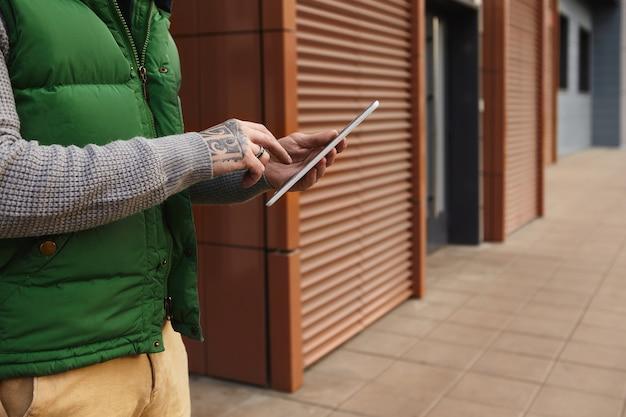 Ritagliata colpo di giovane maschio alla moda irriconoscibile con tatuaggio digitando il messaggio sul computer portatile digitale, chattare online o navigare in internet. primo piano di gadget elettronici nelle mani dell'uomo