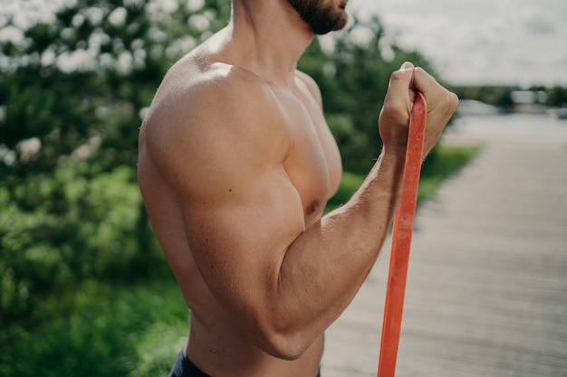 Cropped shot of unrecognizable muscular man has workout biceps exercise stands in profile shows strong muscles