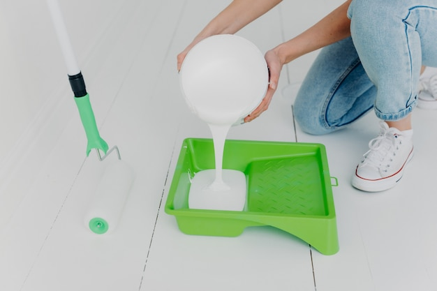 Cropped shot of unrecognizable woman pours white paint in tray