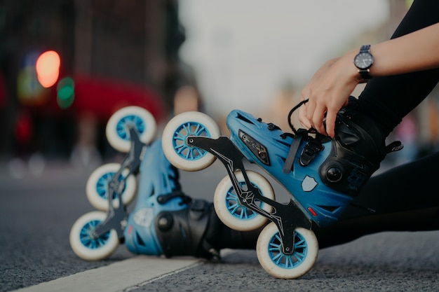 Cropped shot of unrecognizable woman puts on rollerblades poses outdoors on asphalt against blurred background. unknown person wears rollerskates spends free time actively tries new purchase