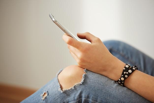 휴대 전화를 들고 여자의 손의 자른 된 샷보기