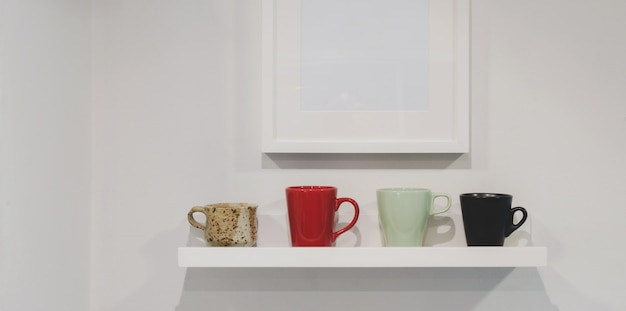 Cropped shot of wall shelf with coffee cups and mock up frame