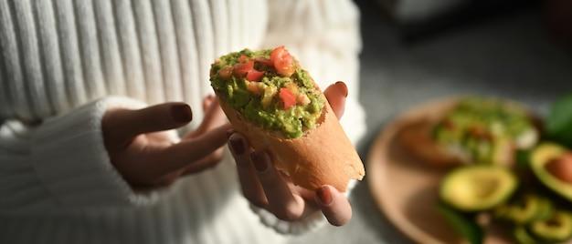 アボカドサンドイッチを持っているクロップドショットの女性。