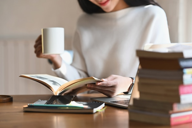 Cropped shot woman holding coffee cup while reading book.