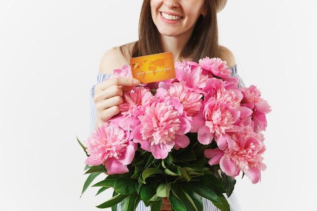 青いドレス、クレジット銀行カード、お金、白い背景で隔離の美しいピンクの牡丹の花の花束を保持している帽子のトリミングされたショットの女性。ビジネス、配達、オンラインショッピングのコンセプト。スペースをコピーします。