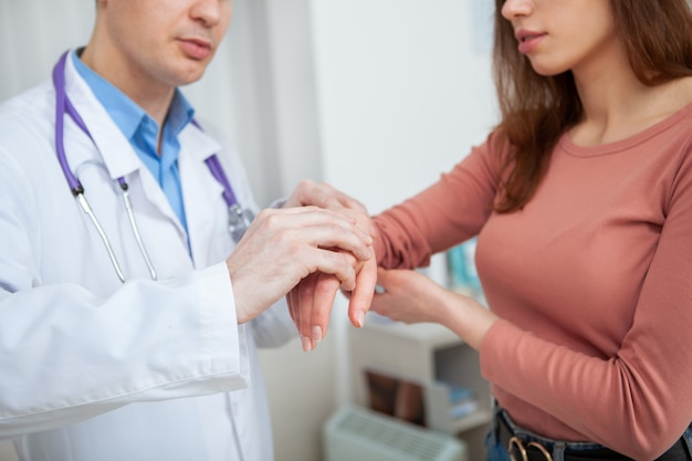 Cropped shot of a woman showing her hurting injured wrist to the doctor