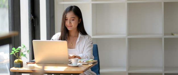 Cropped shot of woman university student focusing on her work with laptop