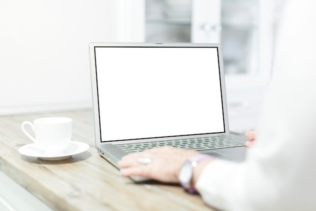 彼女の家で空白の画面でラップトップコンピューターを使用してトリミングされたショットの女性。
