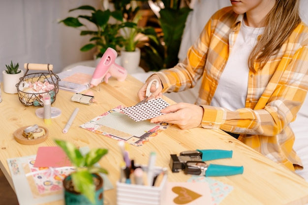 Cropped shot of women making homemade scrapbooking album from paper.