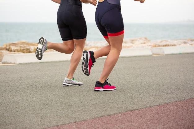 Colpo potato delle donne che corrono sulla riva di mare