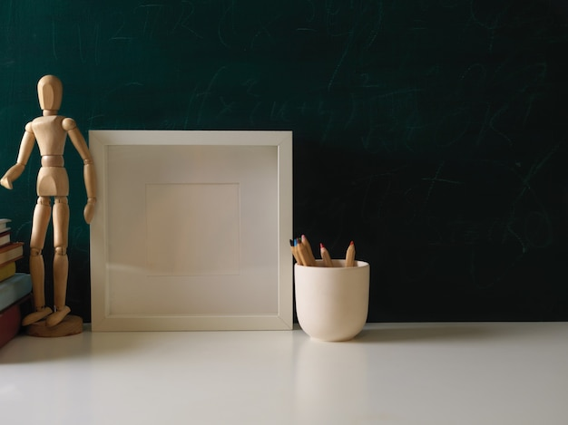 Cropped shot of workspace with mock up frame, pencils, wooden figure and copy space in dark green wall background