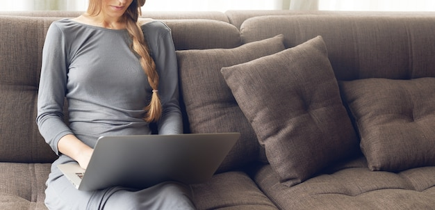 Cropped shot of young blond woman with braid working on a laptop sitting on the comfortable dark sofa at home, backlit warm light. freelance or lifestyle concept.