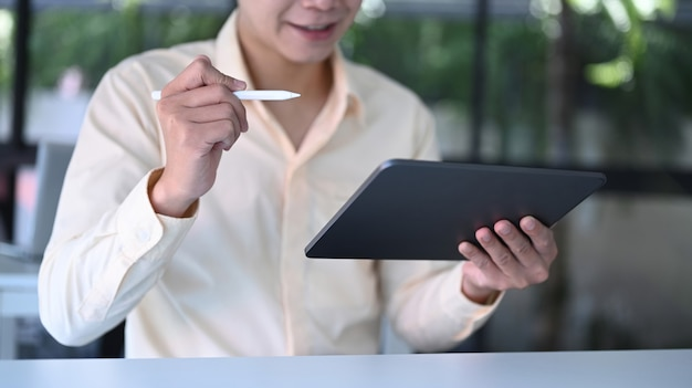 Cropped shot of young businessman smiling and holding digital tablet at office.