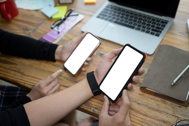 一緒にスマートフォンを使用してクロップドショットの若いカップル。