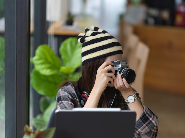 Cropped shot of young female photographer taking a photo in workspace