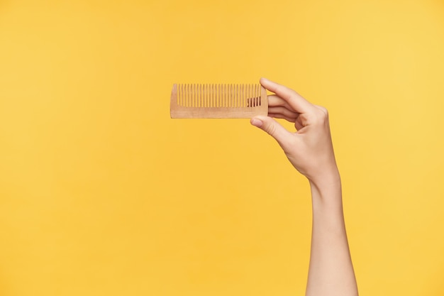 Ritagliata colpo della mano della giovane donna che viene sollevata mentre si tiene la spazzola per capelli in legno con l'indice e il pollice isolati su sfondo arancione