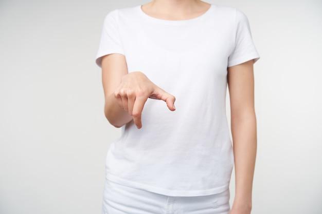 Ritagliata colpo della mano della giovane donna che viene sollevata mentre mostra l'escursione di parola sul linguaggio dei segni, in posa su sfondo bianco. gesti delle mani di persone con problemi di udito.