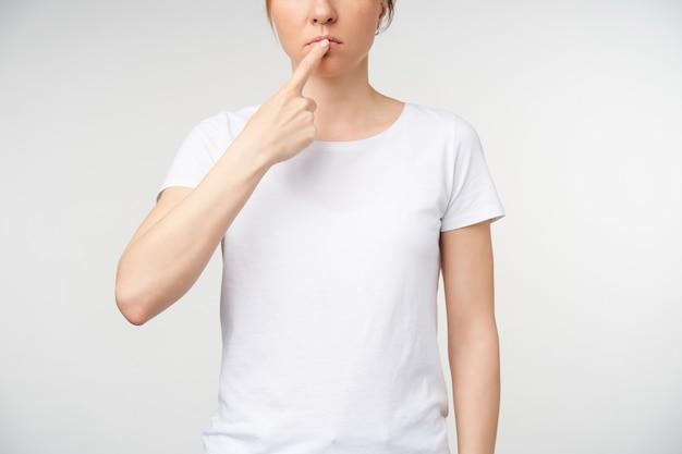 Ritagliata colpo di giovane donna con trucco naturale mantenendo il dito indice sulle labbra mentre mostra la lingua di lavoro sul linguaggio dei segni, in piedi su sfondo bianco